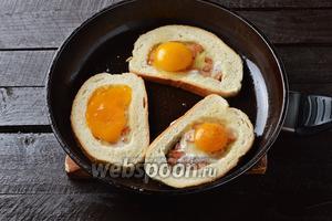 Сверху на колбасу в центр ломтиков хлеба вбить по одному яйцу. Убавить огонь и готовить приблизительно 2-3 минуты, чтобы белки стали матовыми.