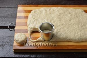 Разделочную доску смазать подсолнечным маслом (1 ст. л.). Раскатать тесто на доске. Толщина теста  1,5 сантиметра. С помощью небольшой выемки вырезать заготовки. Оставить их в тёплом месте на 15 минут.