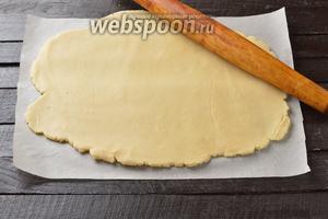 Вынуть тесто и раскатать между двумя листами пергамента. Толщина теста — приблизительно 3 миллиметра. Перенести тесто вместе с нижним пергаментом в форму с бортиками. Сформировать бортики из теста. Диаметр формы 26 сантиметров. У меня овальная форма. Отправить тесто вместе с формой в холодильник на 30 минут.