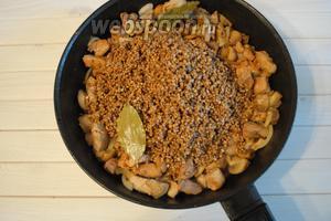 Продолжая обжаривать, добавить лук, смесь специй для мяса (1 ст. л.) и соль по вкусу, и 2 лавровых листа. Перемешать. Выложить подготовленную гречневую крупу 2 стакана.