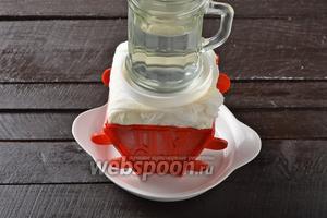 Завернуть края марли на творожную массу. Сверху выложить пластмассовую крышку или какой-то другой плоский предмет подходящей формы, а на него — небольшой груз, например, стакан или банку с водой. Отправить в холодильник на 12 часов, периодически сливая образовавшуюся на тарелке жидкость.