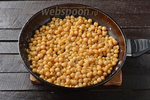 Выложить нут на горячую сковороду с подсолнечным маслом (2 ст. л.) и жарить на сильном огне, помешивая, 4-5 минут.