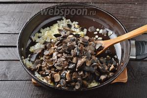 1 лук почистить, нарезать небольшими кубиками и обжарить на растительном масле (2 ст. л.) до лёгкой золотистости. Добавить подготовленные грибы. Жарить, помешивая, 8-10 минут.