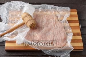 Куриное филе (2 штучки) разрезать «книжкой», сформировав 1 тонкий пласт. Отбить пласт между 2 слоями пищевой плёнки до толщины 2-3 миллиметра.