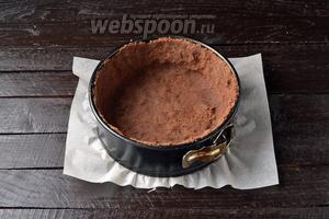 Форму диаметром 20 сантиметров выложить пергаментом. В форму выложить 2/3 части крошки и сформировать из неё дно и стенки пирога, хорошо утрамбовывая и прижимая её ко дну и стенкам формы. Отправить в холодильник на 20 минут.