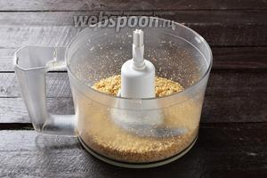 Орехи 110 г поместить в чашу кухонного комбайна (насадка металлический нож) и измельчить до мелкой крошки.