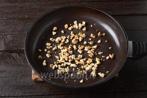 Орехи 100 г крупно порубить и слегка обжарить на сухой горячей сковороде.