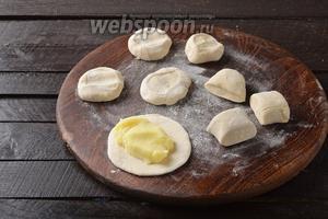 Разделить тесто на небольшие кусочки. Каждый кусочек раскатать в лепёшку, толщиной приблизительно 3 миллиметра. На середину раскатанной лепёшки выложить 1 столовую ложку начинки.