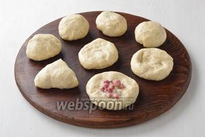 Обомнуть подошедшее тесто и разделить на кусочки весом по 50 грамм. Сформировать из каждого кусочка теста лепёшку. На середину лепёшки выложить 1 столовую ложку начинки. Сформировать пирожки.