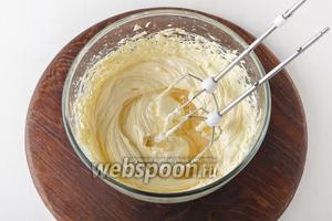 Порциями добавлять охлаждённый сахарный сироп в масло, постоянно взбивая, пока он не закончится.