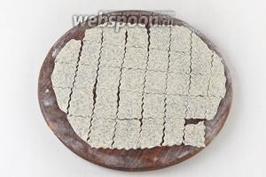 На слегка подпылённой мукой доске раскатать тесто толщиной 1 миллиметр. Разрезать пласт теста на небольшие кусочки.