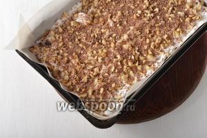 Форму размером 20х30 сантиметров выложить пергаментом. В форму ложкой выложить 1/3 часть теста и разровнять. Сверху выложить и разровнять 1/3 часть белкового теста, посыпать 1/3 частью рубленых орехов (всего 1 стакан орехов) и 1/3 частью натёртого на крупной тёрке шоколада (всего шоколада 50 г). Коржи у нас выпекаются один за другим, а не все вместе, поэтому каждый раз следует готовить свежую белковую часть теста, чтобы она не осела. Для белковой части теста (это 1/3 часть от всех продуктов на 1 раз) взбить 2 белка до устойчивой пены. Постепенно добавить 65 грамм сахара, постоянно взбивая, а в конце подмешать 0,5 столовой ложки картофельного крахмала.
