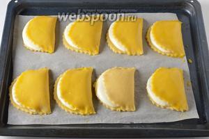 Переложить сочни на противень с пергаментной бумагой. Смазать желтком (остался от приготовления начинки), разболтанным с 2 столовыми ложками воды.