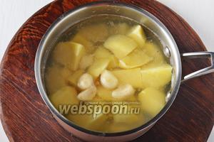Поместить картофель и очищенный чеснок (1 головку) в кипящую подсоленную воду. Довести до кипения и варить 6-7 минут (до полуготовности).