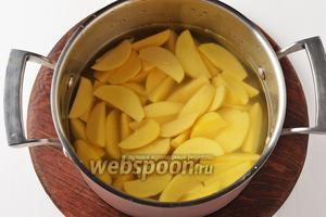 Картофель 750 г очистить. Разрезать каждый клубень на 6-8 долек, выложить в кастрюлю с холодной водой. На большом огне довести до кипения и проварить 1 минуту. Слить воду.