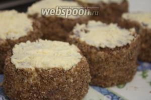 Верхушку пирожного также смазываем кремом и посыпаем крошками бисквита.