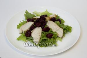 Сверху на салат раскладываем пластинки куриного филе, между ними — вишенки. В середине делаем из ягод небольшую горку.