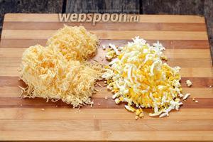 2 яйца отварить вкрутую, очистить и натереть на крупной тёрке. 200 г сыра натереть на мелкой тёрке.