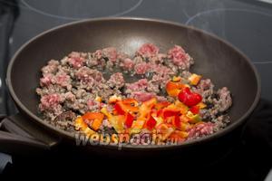 Добавляем измельчённый болгарский перец, перемешиваем и тушим вместе ещё 5 минут.