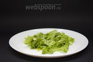 1 пучок салата режем на кусочки или рвём руками. На дно 2 тарелок выкладываем по половине пучка измельчённых салатных листьев.