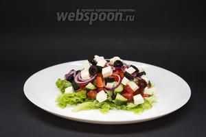 100 грамм сыра фетакса (или феты, или брынзы) режем маленькими кубиками, 12 штук маслин — тонкими кружочками. Украшаем всю поверхность салата.