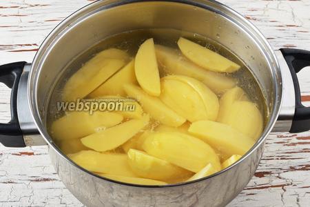Картофель (1 кг) очистить, промыть, разрезать на 4 части и отварить до готовности вместе с солью (1 ч. л.).