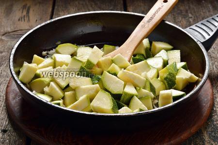 Цукини 400 г вымыть, нарезать средними кусочками и выложить в сковороду к луку. Готовить под крышкой, иногда помешивая, 7-8 минут.