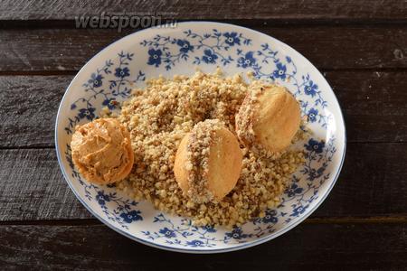 Сформировать орешки, соединив половинки скорлупок кремом. Выступающий на швах крем посыпать остальными молотыми орехами (50 грамм).