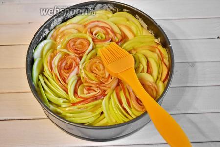 Растопить оставшиеся 20 грамм сливочного масла и нанести кулинарной кистью на яблоки.