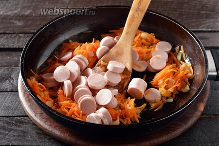 Сосиски (150 грамм) очистить от оболочки, нарезать кружочками и выложить к овощами. Готовить, помешивая, 2-3 минуты. Выложить содержимое сковороды в кастрюлю. Проварить всё 4-5 минут.