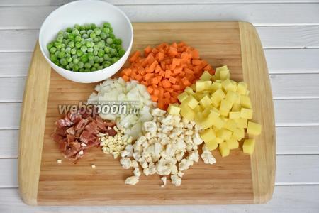 Подготовить овощи, порезать кубиком 1 морковь, 2 картофелины, 1 луковицу. 200 грамм цветной капусты разобрать на соцветия, измельчить 2 зубчика чеснока, порезать 250 грамм бекона.