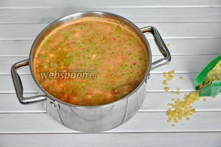 Добавить к овощам 200 грамм резанных томатов (вместе с томатным соком) и 1,5 литра мясного бульона. Варить суп на медленном огне до готовности картофеля (20-30 минут). Затем всыпать 150 грамм мелких фигурных макарон. Довести суп до кипения, дать покипеть 3 минуты и отключить. Оставить суп настояться минут 15-20. Подавать суп, посыпав по вкусу зеленью. По желанию можно добавить в тарелку с супом тёртый сыр.