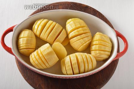Смазать картофель со всех сторон подсолнечным маслом 2-3 ст. л. и посыпать солью (масло и соль 1 ч. л. должны попасть и во все разрезы картофеля). Выложить картофель в форму для выпекания.