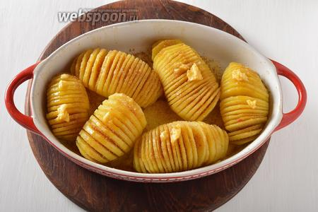 Готовить в разогретой до 200°С духовке 35 минут. Вынуть форму, посыпать картофель чёрным молотым перцем (0,2 ч. л.), сухарями (2 ст. л.) и смазать сливочным маслом (2 ст. л.) таким образом, чтобы масло попало во все разрезы. Отправить в духовку ещё на 15 минут.