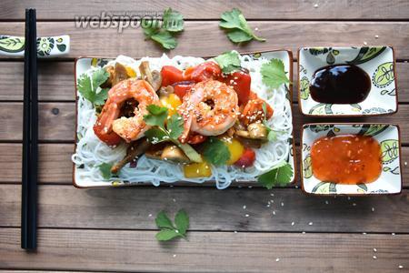 На порционное блюдо выложить рисовую лапшу, в центр — обжаренные овощи. Сверху на овощи выложить креветки.    Подайте к лапше соус Терияки и кисло-сладкий соус, чтобы каждый мог выбрать соус по вкусу.