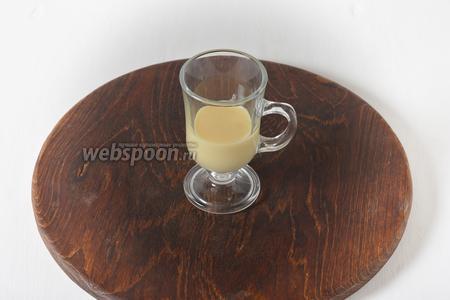 В айриш-стакан выложить на 1/3 его высоты сгущённое молоко (3 ст. л.), стараясь не запачкать стенки.