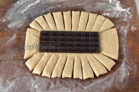 Раскатать тесто в овальный пласт толщиной 0,6-0,7 сантиметра. На середину выложить плитку шоколада. Сделать на тесте насечки-полоски.