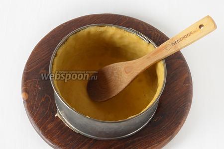 Форму (диаметром 17-18 сантиметров) выложить пергаментом. Раскатать тесто между двумя слоями пищевой плёнки и выложить в форму, формируя дно и высокие бортики (6-7 сантиметров).