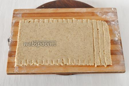 Раскатать тесто толщиной 8 миллиметров и нарезать его полосками 1,5х15 сантиметров.