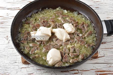 Добавить в сковороду плавленый сливочный сыр (100 г). Перемешать и проварить 1-2 минуты, чтобы сыр полностью расплавился.