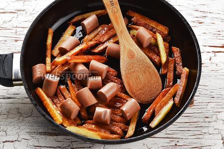 Удалить оболочку у сосисок и нарезать их небольшими кусочками. Выложить 2 сосиски к картофелю. Перемешать и жарить 1-2 минуты до слегка зажаристой корочки. Для проверки готовности картофеля, следует выбрать самый толстый брусок картофеля и проткнуть его вилкой. Если он готов, то готов и весь картофель. Приправить картофель солью (0,5 ч. л.) и перемешать.