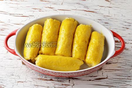 Форму для запекания смазать сливочным маслом (1 ст. л.). Выложить рулетики в форму. Каждый рулетик смазать сверху 1 желтком.