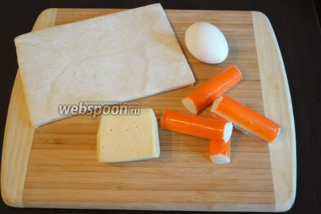 Подготовить небольшой набор продуктов: крабовые палочки, слоёное тесто, сыр твёрдых сортов, желток для смазывания теста.