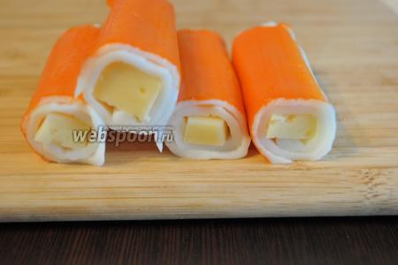 100 грамм сыра нарезать брусочками 1х1 см, по длине крабовых палочек. Каждый брусочек сыра завернуть в крабовую палочку, вернув ей первоначальную форму.