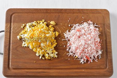 2 яйца отварить вкрутую, очистить и мелко порубить. Крабовые палочки 100 г натереть на средней тёрке.