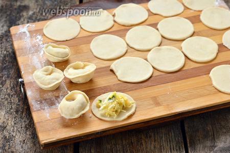 На каждый кружок выложить 1 чайную ложку начинки и сформировать пельмени.