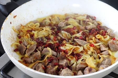 Когда лук закарамелизуется, ложкой, аккуратно, чуть отодвиньте его на край сковороды, положите в освободившее место мясо и, перемешивая, чуть обжарьте его. Затем так же аккуратно смешайте с луком, сверху присыпьте барбарис (50 грамм), залейте оставшиеся 0.5 стаканами бульона и прикройте крышкой.