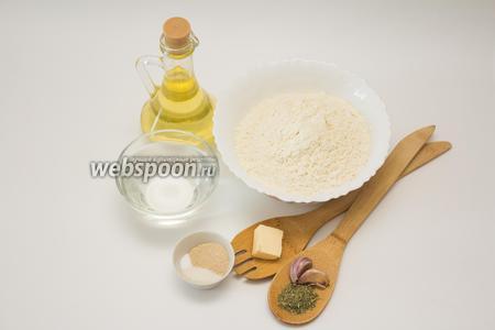 Для приготовления хлеба нам понадобится ряд самых простых ингредиентов: муки пшеничной 340 грамм (её можно предварительно просеять), тёплой воды 200 мл, сливочного масла 10 грамм, сухих дрожжей 5 грамм, а также 2 чайные ложки сахара и 1 чайная ложка соли. Для корочки отмеряем 2 столовые ложки растительного масла, по 1 щепотке любимых сушёных трав (я использую розмарин и базилик), а также 1-2 зубчика чеснока. Можно добавить щепотку соли.