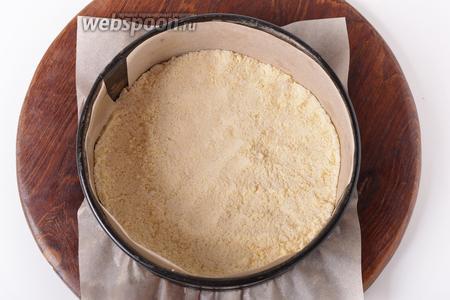 Форму диаметром 20-22 сантиметра застелить пергаментом. На дно формы высыпать 1/4 часть крошки и разровнять её.