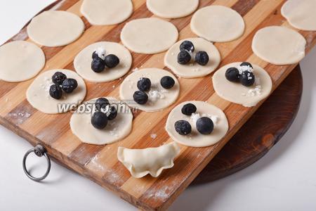 На середину каждого кружка выложить по 3 промытых и просушенных ягод тёрна и немного сахара (всего 50 грамм). Сформировать вареники.